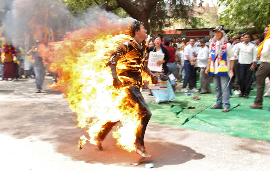 Jamphel Yeshi, a Tibetan exile, runs after setting himself on fire during a protest against the upcoming visit of Chinese President Hu in New Delhi