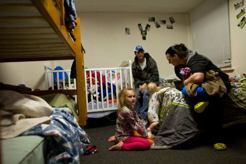 """We lost everything,"" said Ms. Kipp, 25, whose husband works for an oil services company. ""We needed somewhere to go."" Left, she and Mr. Kipp prepare their two children, Emily and Payton, for bed in their room at the shelter.Credit: Matthew Staver for The New York Times"