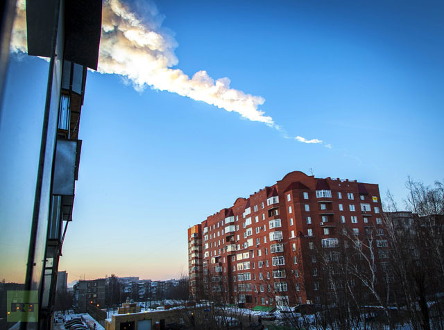 The trail of a falling object is seen above a residential apartment block in the Urals city of Chelyabinsk, on February 15, 2013.(AFP Photo / Oleg Kargopolov)