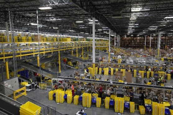 Workers process orders on assembly lines in the Chattanooga Amazon fulfillment center. Photo by Doug Strickland.