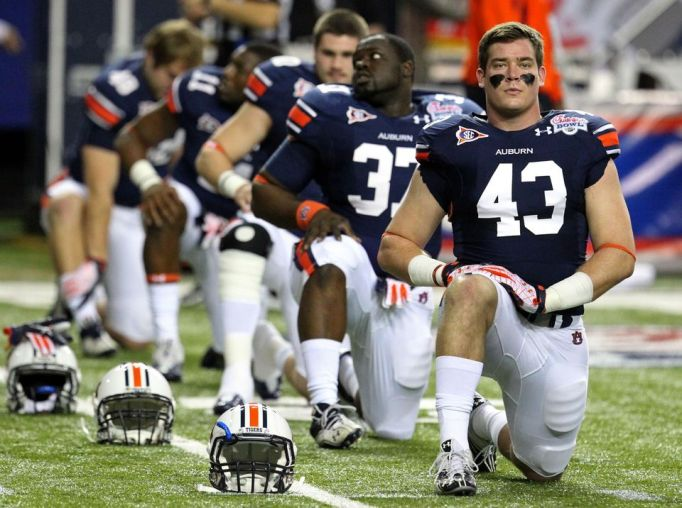 Auburn H-Back Philip Lutzenkirchen (43) stretches with teammates before the Chick-fil-A Bowl game in the Georgia Dome Saturday night in Atlanta, Ga., December 31, 2011. Lutzenkirchen is a native of Marietta, graduating from Lassiter High School. AJC photo by Jason Getz