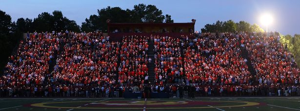 Friends, family, teammates and fans hold candles in memory of Philip Lutzenkirchen during a memorial service at Lassiter High School in east Cobb on Wednesday evening July 2, 2014. Lutzenkirchen was a star football player at Lassiter and Auburn who died in a car accident. BEN GRAY / BGRAY@AJC.COM