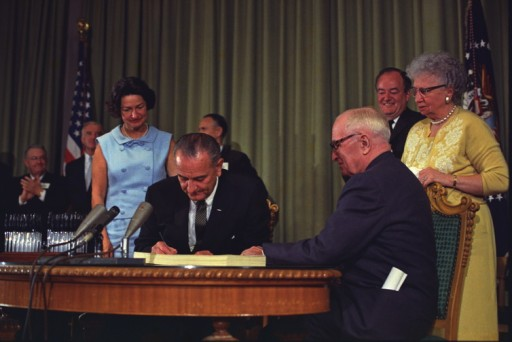 President Lyndon B. Johnson signs the Medicare Bill. President Harry S. Truman is seated next to him. Image courtesy of LBJ Library